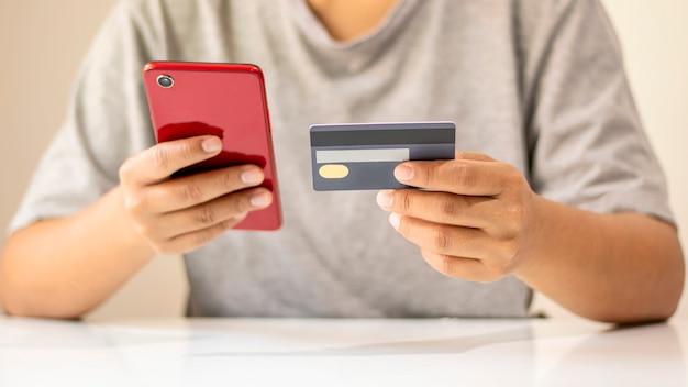 Asiatischer mann, der per kreditkarte online zahlt, während er zu hause im internet bestellt, transaktionsidee unter verwendung der mobile-banking-anwendung.