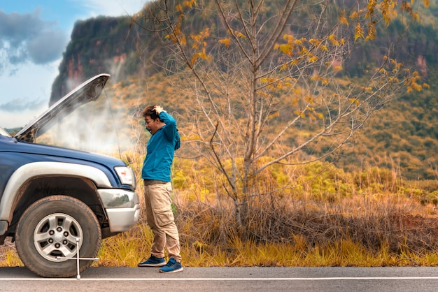 Asiatischer mann, der probleme mit seinem defekten auto hat