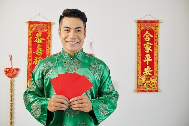 Asiatischer mann, der rote glücksgeldumschläge zeigt