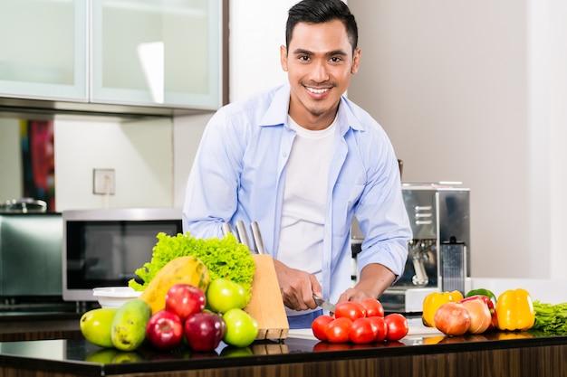 Asiatischer mann, der salat in der küche schneidet
