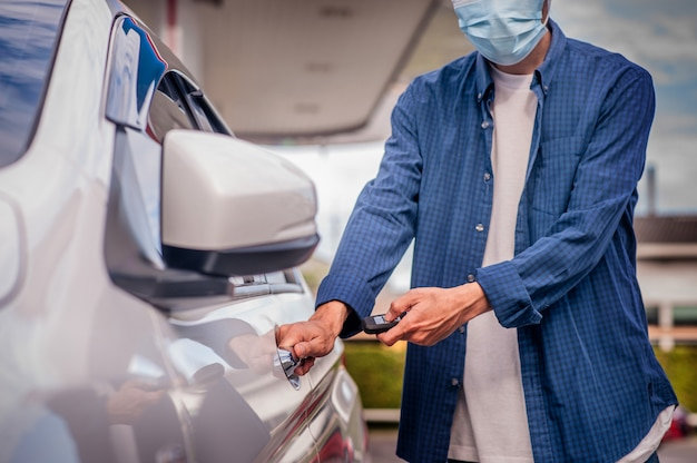 Asiatischer mann, der schlüssel offene autotür hält