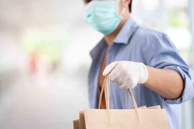 Asiatischer mann, der schützende gesichtsmaske hält, die einkaufstasche hält