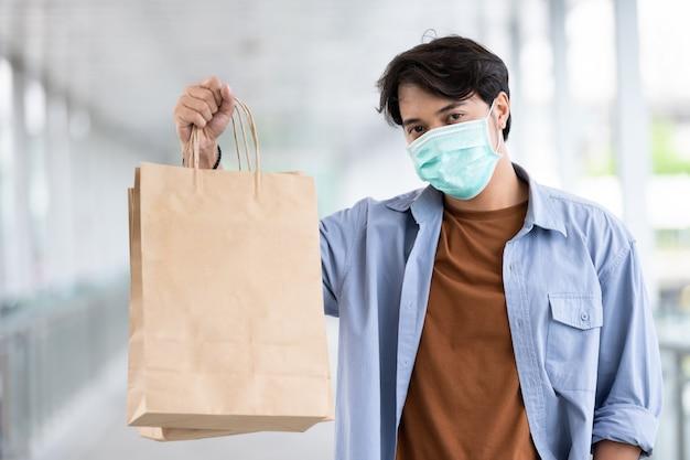 Asiatischer mann, der schützende gesichtsmaske hält, die einkaufstasche während des ausbruchs der coronavirus-krankheit hält, neuer normaler lebensstil.