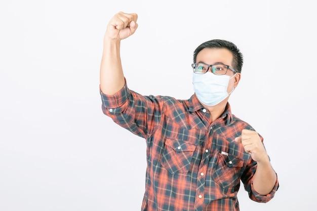 Asiatischer mann, der schützende gesichtsmaske in aktion des sieges trägt