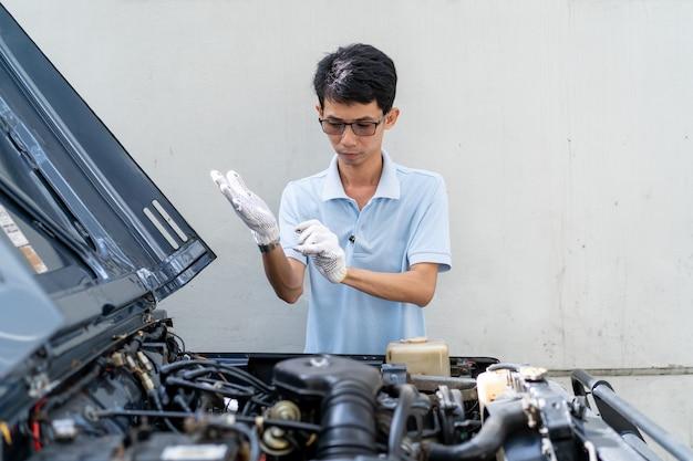 Asiatischer mann, der schutzhandschuhe trägt, bevor ein auto überprüft wird.