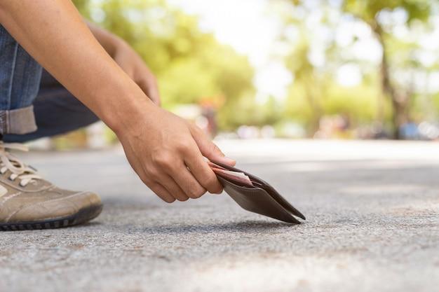 Asiatischer mann, der schwarze geldbörse auf der straße in der touristenattraktion auswählt