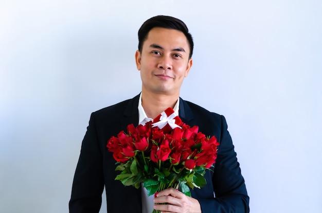 Asiatischer mann, der schwarzen anzug trägt, der einen blumenstrauß der roten rosen und des roten geschenkkastens lokalisiert im weißen hintergrund für jubiläums- oder valentinstagkonzept hält.