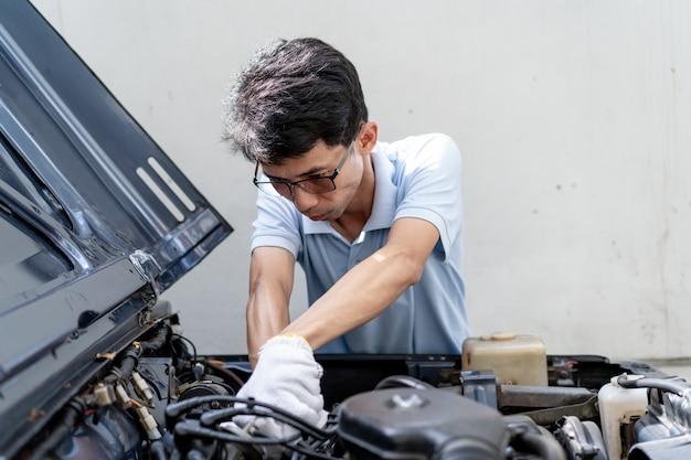Asiatischer mann, der sein altes auto kontrolliert.