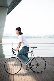 Asiatischer mann, der sein fahrrad fährt
