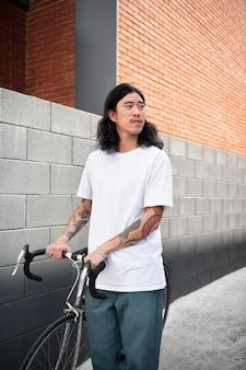 Asiatischer mann, der sein fahrrad hält