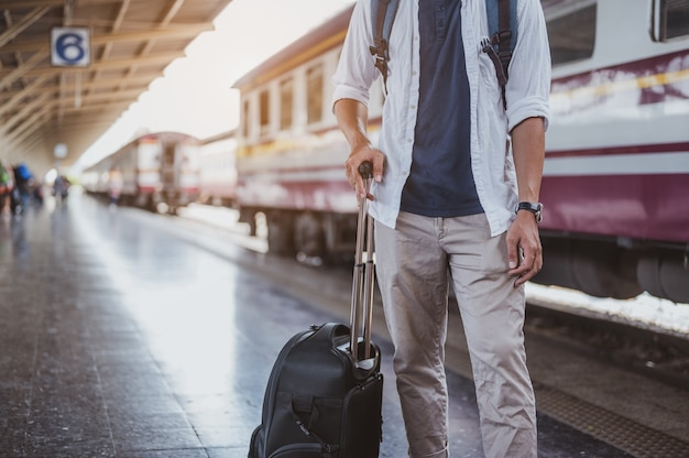 Asiatischer mann, der sein gepäck im bahnhof trägt. reisekonzept. mann reisender tourist zu fuß am bahnhof.