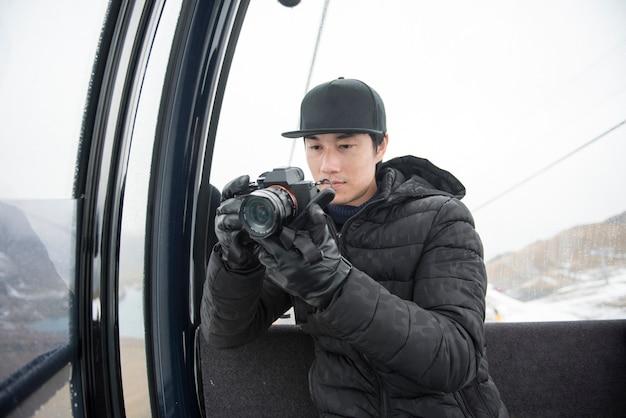 Asiatischer mann, der seine kamera verwendet, während sie in der drahtseilbahn sitzen