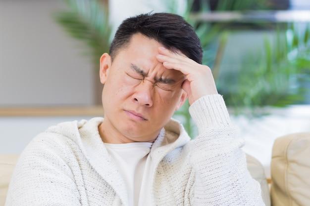 Asiatischer mann, der seinen kopf mit starken kopfschmerzen zu hause in einem zimmer auf der couch hält
