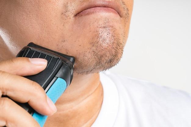 Asiatischer mann, der seinen neuen kurzen bart rasiert