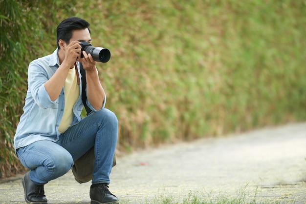 Asiatischer mann, der sich unten in park duckt und fotos mit digitalkamera macht