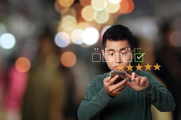 Asiatischer mann, der smartphone mit kundenservicebewertung in zufriedenheit verwendet.