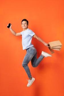Asiatischer mann, der smartphone und einkaufstasche beim springen hält