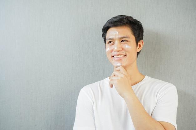 Asiatischer mann, der sonnenschutz-uv-schutz auf gesicht und lächeln anwendet