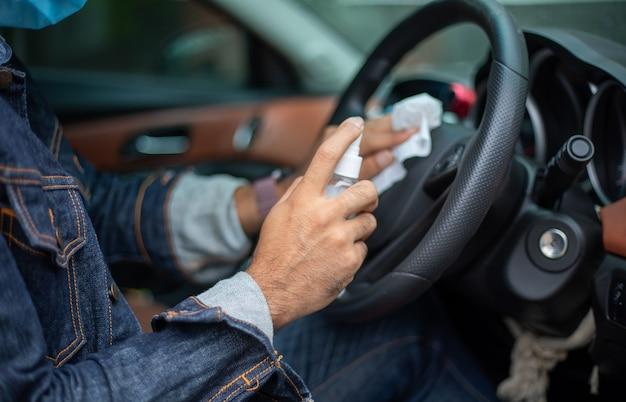 Asiatischer mann, der sprühalkohol verwendet, um das auto für coronavirus-schutz zu reinigen