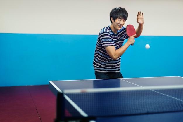Asiatischer mann, der tischtennis spielt