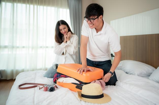 Asiatischer mann, der versucht, alle kleidung zum packen seines orange koffers vor ferien zu passen