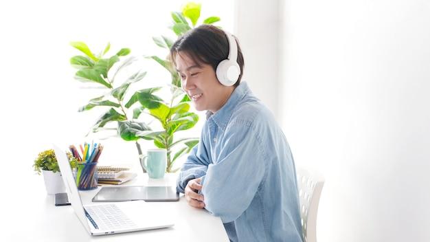 Asiatischer mann, der videoanruf zum geschäftsteam mit weißen kopfhörern auf und pflanzen im hintergrund macht