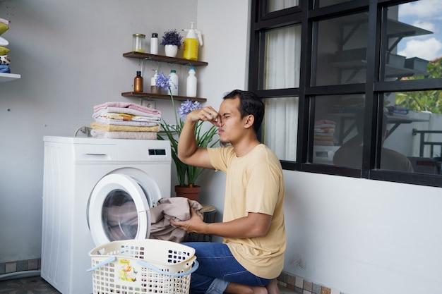 Asiatischer mann, der wäsche zu hause beim laden von kleidung in den schlechten geruch der waschmaschine macht