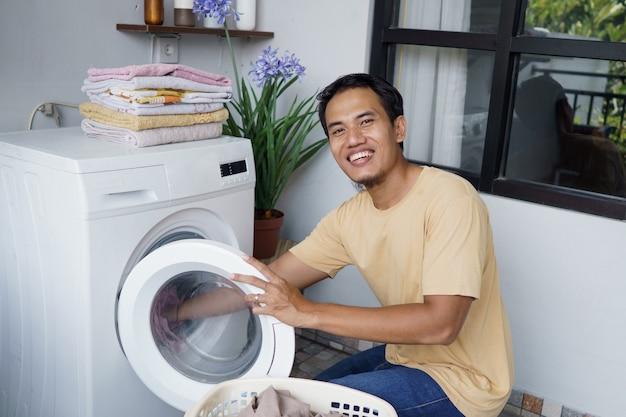 Asiatischer mann, der wäsche zu hause beim laden von kleidung in die waschmaschine macht
