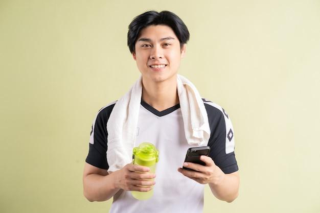 Asiatischer mann, der wasser und smartphone in der hand hält