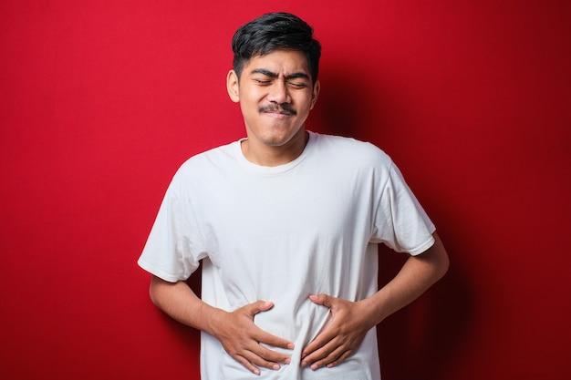 Asiatischer mann, der weißes t-shirt durchfall-gesundheitsprobleme warnt, hält seinen bauch über rotem hintergrund