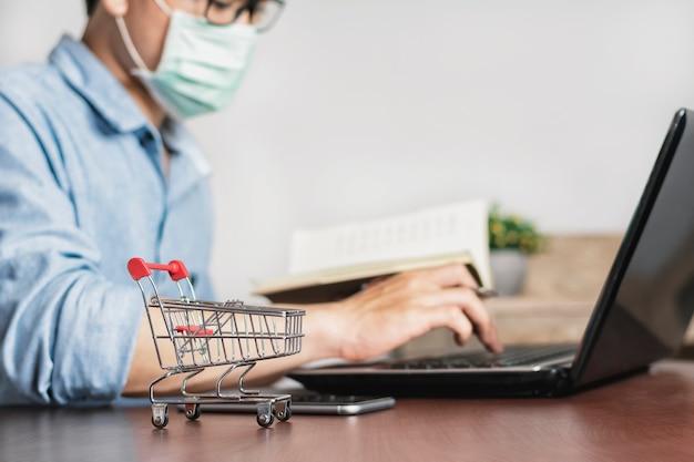 Asiatischer mann, der zu hause arbeitet und eine maske trägt, um gegen corona-virus zu schützen