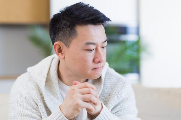 Asiatischer mann, der zu hause auf dem sofa sitzt und sich sorgen um probleme und depressionen macht