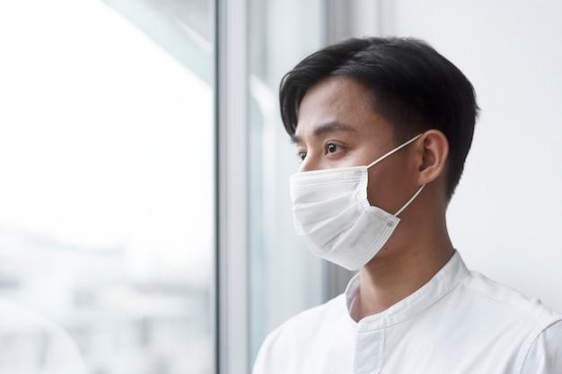 Asiatischer mann, der zu hause eine gesichtsmaske trägt