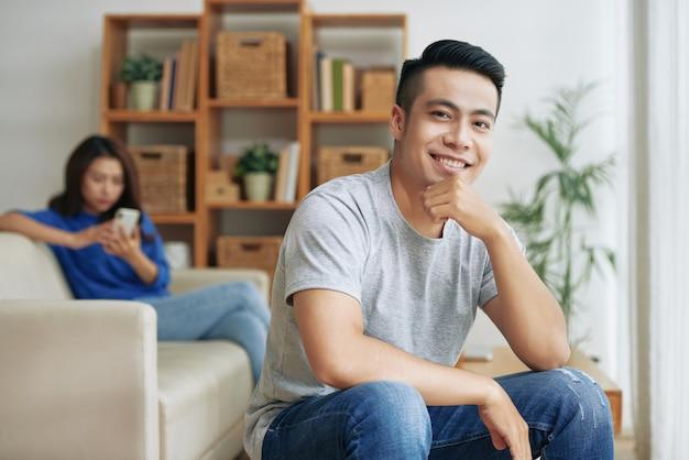 Asiatischer mann, der zu hause mit dem kinn an hand und frau mit smartphone hinter ihm auf couch sitzt