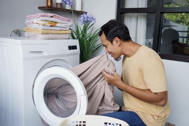 Asiatischer mann, der zu hause wäsche wäscht und kleidung in die waschmaschine lädt, riecht die wäsche
