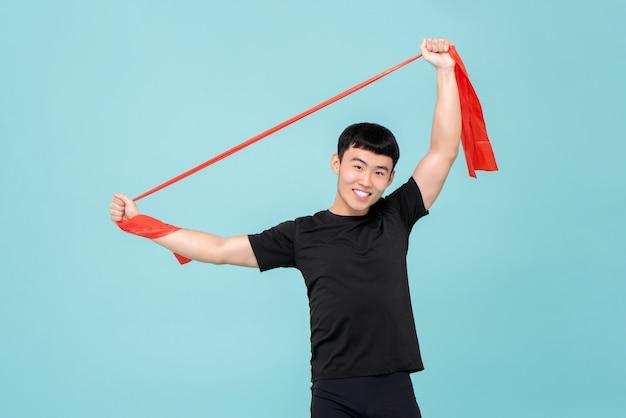 Asiatischer mann des athleten, der durch die verwendung des widerstandbandes vor übung aufwärmt