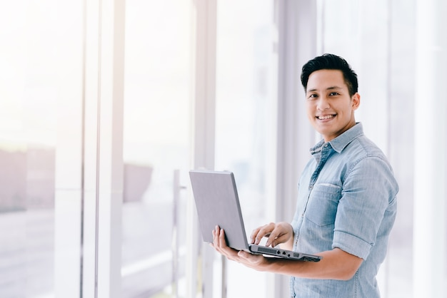 Asiatischer mann des glücklichen lächelns, der laptop mit positivem gefühl im büro verwendet