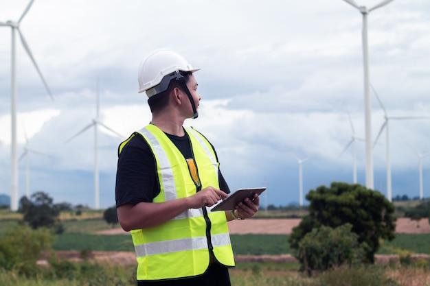 Asiatischer mann des ingenieurs, der laptoptablette mit windkraftanlage hält