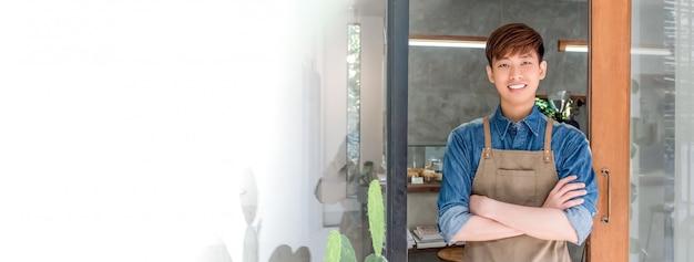 Asiatischer mann des jungen unternehmers an der haustür seines eigenen cafés