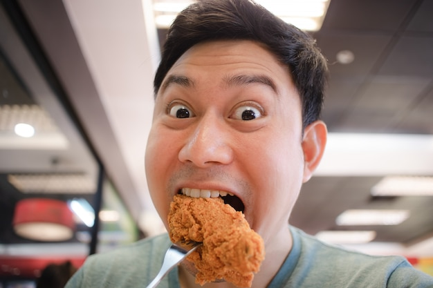 Asiatischer mann des lustigen gesichtes essen gebratenes huhn.