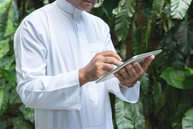 Asiatischer mann des muslimischen geschäfts, der tablette verwendet und im grünen café steht, tragen muslimisches kleid, freiberufliches geschäftskonzept.