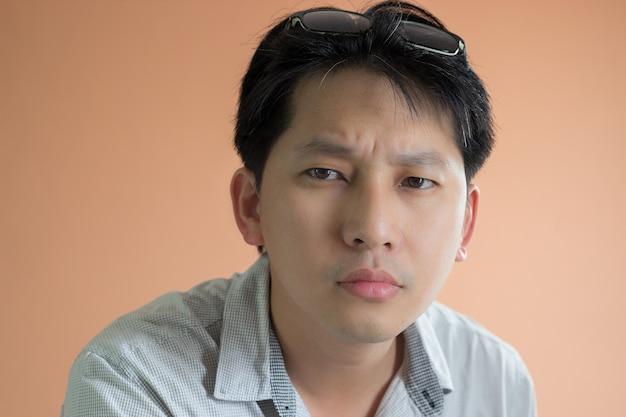 Asiatischer mann des nahaufnahmeporträts, der etwas schauen schaut, wie tief für einige ideen denkend