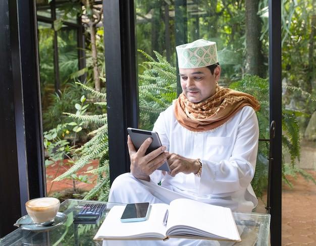 Asiatischer mann des pakistanischen geschäfts, der tablette verwendet, die im grünen café sitzt