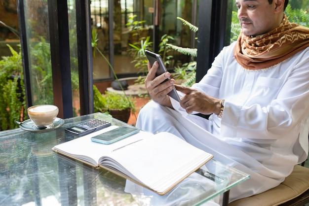 Asiatischer mann des pakistanischen geschäfts, der tablette verwendet und im grünen café sitzt, tragen muslimisches kleid