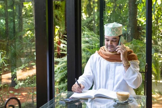 Asiatischer mann des pakistanischen geschäfts im lässigen tragen lässig schreiben auf notizbuch unter verwendung des intelligenten mobiltelefons mit tasse kaffee im café, freiberufliches geschäftskonzept.