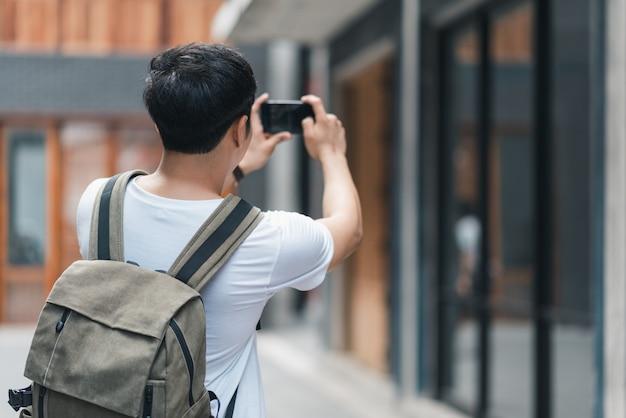 Asiatischer mann des reisenden, der handy für verwendet, machen ein foto, während er urlaubsreise in peking, china verbringt
