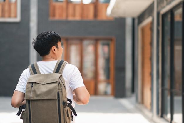 Asiatischer mann des reisenden, der in peking, china reist und geht