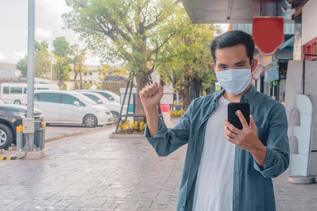 Asiatischer mann eine tragende gesichtsmaske, die handy-lebensstil neue normale soziale distanzierung hält