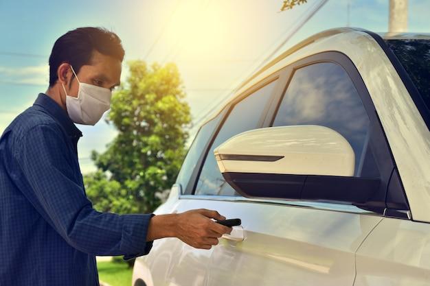 Asiatischer mann eine tragende gesichtsmaske, die schlüsselauto hält, öffnet autotür