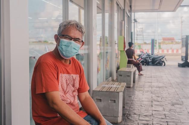 Asiatischer mann eine tragende gesichtsmaske lebensstil neue normale soziale distanzierung
